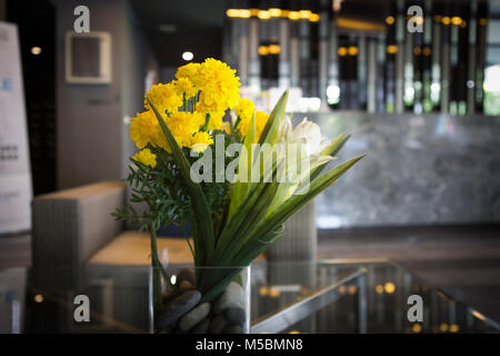 a glass vase of marigold put on the table in lobby of building - Stock Photo