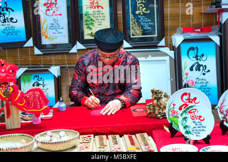 Vietnamese scholar writes calligraphy at lunar new year calligraphy festival is a popular tradition during Tet holiday - Stock Photo