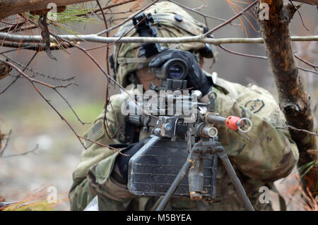 A Soldier assigned to the 3rd Brigade Combat Team, 25th Infantry Division uses an M249 machine gun at a defensive - Stock Photo