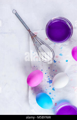 Easy way to paint Easter eggs. Using a whisk and food dye. Minimalist Easter decorations from above. Copy space. - Stock Photo