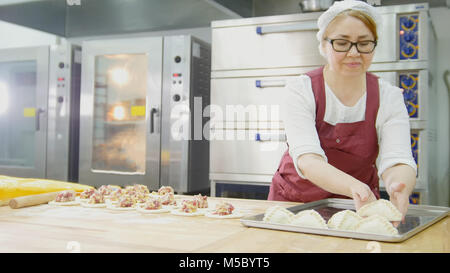Adult woman in glasses and apron bakes cakes in the bakery face - Stock Photo