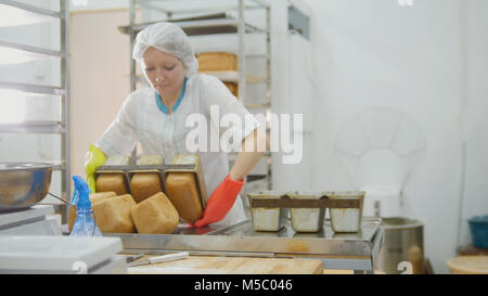 Female bakes bread on commercial kitchen