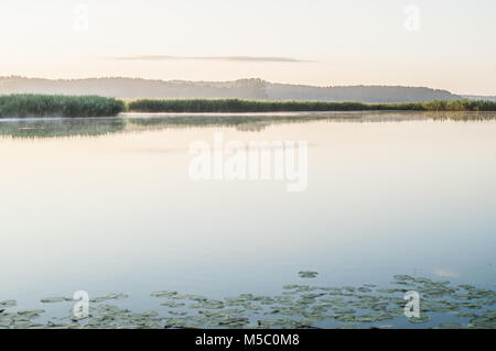 Crystal clear lake. Early morning lights. - Stock Photo