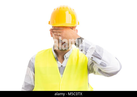 Foreman or contractor covering his eyes wearing yellow hardhat and reflective vest isolated on white background - Stock Photo