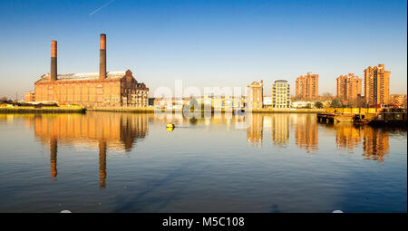 Lots Road Power Station and the World's End high-rise council estate are reflected in the waters of the River Thames - Stock Photo