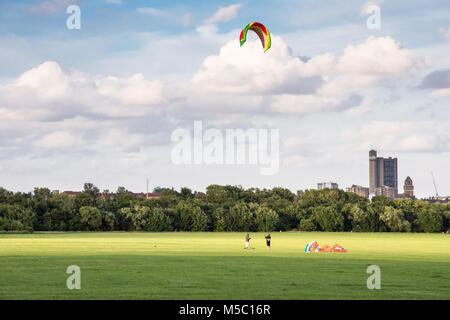 London, England - July 10, 2016: Two people fly a large kite on Wormwood Scrubs common in west London, with the - Stock Photo