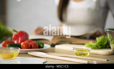 Close-up of girl flipping through cooking book pages, choosing salad recipe, stock footage - Stock Photo