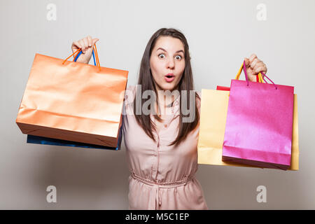 Beautiful woman is in shock from purchases she made on shopping - Stock Photo