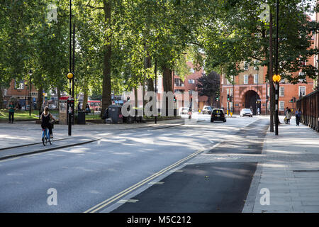 London, England - July 25, 2016: Cyclists use the newly introduced 'segregated' stepped cycle lanes on Pancras Road - Stock Photo