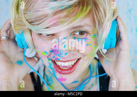 Young woman with paint in her face is listening to music - Stock Photo