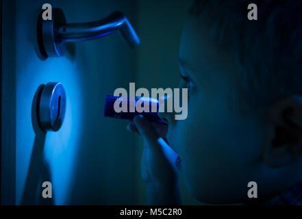 Junge im dunklen Zimmer blickt im Schein der Taschenlampe durch ein Schlüsselloch. - Stock Photo