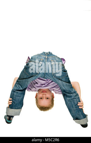 Boy standing with his back to the camera, standing in front of him, bending over his pawed legs towards the camera - Stock Photo
