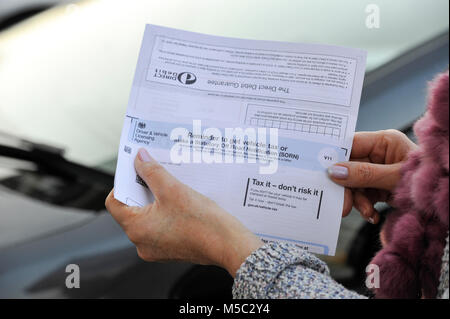 Woman checking her DVLA car vehicle Tax Renewal reminder notice - Stock Photo