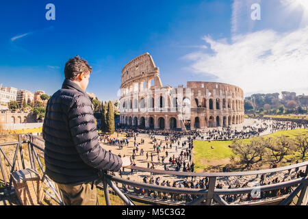 Male tourist enjyoing the view at the Colosseum in Rome, Italy - Stock Photo