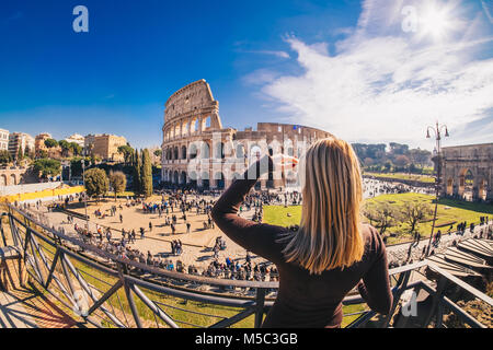 Woman tourist enjoying the view of the Roman Colosseum in Rome, Italy - Stock Photo