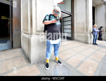 London, England, UK. Interestingly-dressed woman in sunglasses looking at her mobile phone - Stock Photo