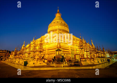 One of the largest pagodas in Bagan, the golden Shwezigon Pagoda in Nyaung U, illuminated at night - Stock Photo