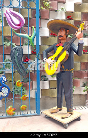 A quirky artistic mannequin of a man in a sombrero strumming the guitar stands on a street in the Zona Rosa neighborhood - Stock Photo