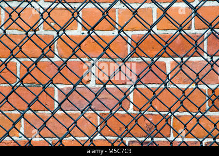 brick wall behind a  chain link fence. Does it mean keep out or is something meant to be kept in? - Stock Photo