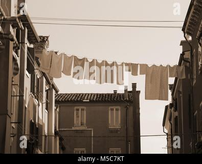many hanging clothes out of house of an european city - Stock Photo