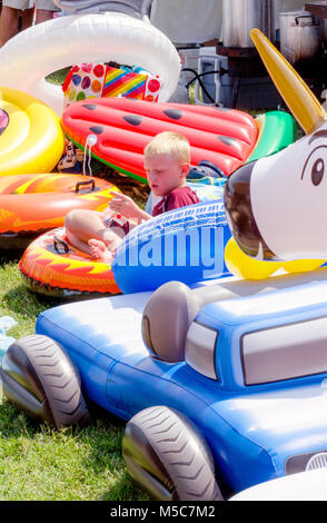 Aug 5, 2017 Buchanan MI; child sits in a soft pile of inflatable toys, the most comfortable spot! - Stock Photo