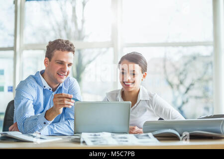 Young businesspeople discussing over laptop at desk in office - Stock Photo