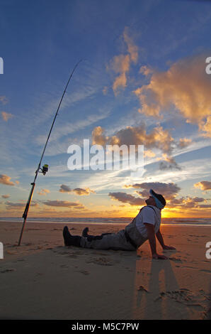 surf fishing scene at sunset on a beach. - Stock Photo
