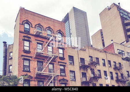 Vintage toned picture of buildings with fire escapes in the New York City, USA. - Stock Photo
