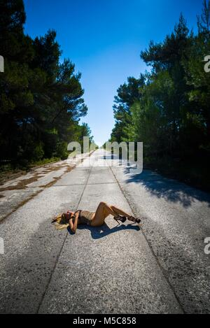Young woman legs heels lying on her back on empty road - Stock Photo