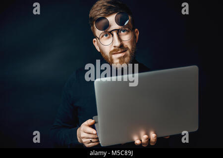 Portrait of handsome brunette bearded man working in office using silver laptop - Stock Photo