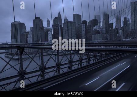 New York City Manhattan downtown skyline from Brooklyn Bridge on moody day - Stock Photo
