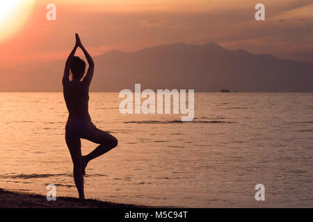 Woman practicing yoga tree position. Sunset over sea in the background. - Stock Photo