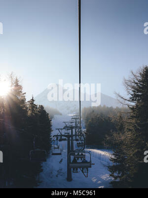 Sun through pine trees as chairlift ascent at Italian ski area covered in snow  - winter sports concept - Stock Photo