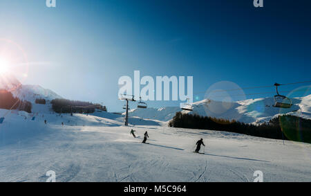 Unidentifiable skiers at ski resort in Pila, Valle d'Aosta, Italy with chairlift and mountain backdrop and copy - Stock Photo
