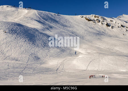 Steep gradient piste in Italian Alps against a beautiful blue sky - Pila, Vale d'Aosta, Italy - Stock Photo