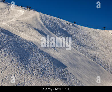 Steep gradient piste in Italian Alps with lone expert snowboarder heading down, against a beautiful blue sky - Pila, - Stock Photo