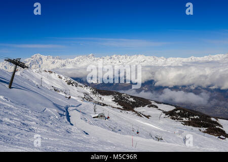 Pila, Aosta, Italy - Feb 19, 2018: Chairlift at Italian ski area of Pila on snow covered Alps and pine trees during - Stock Photo
