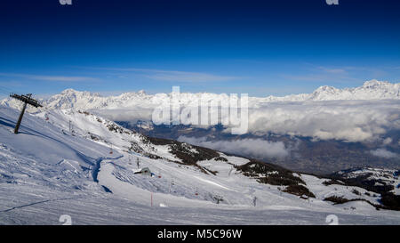 Chairlift at Italian ski area of Pila on snow covered Alps and pine trees during the winter with Mt. Blanc in France - Stock Photo