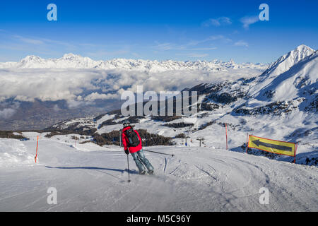 Pila, Aosta, Italy - Feb 19, 2018: One skier in jeans going downhill a piste with panoramic view of wide and groomed - Stock Photo
