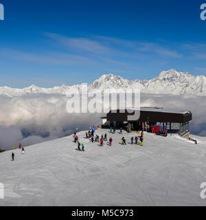 Pila, Aosta, Italy - Feb 19, 2018: Chairlift at Italian ski area of Pila on freshly groomed snow covered Alps above - Stock Photo