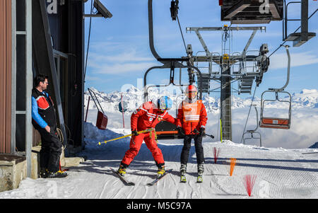 Pila, Aosta, Italy - Feb 19, 2018: Older man and teenager get off chairlift at ski resort with majestic Italian - Stock Photo
