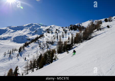 Pila, Aosta, Italy - Feb 19, 2018: Steep gradient piste in Italian Alps with lone expert snowboarder heading down, - Stock Photo