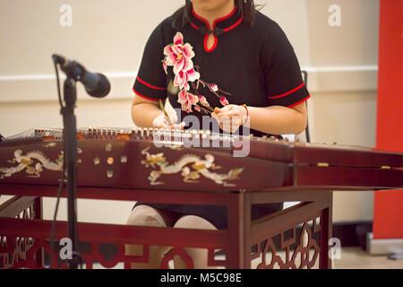 Girl is playing Chinese cymbalo. - Stock Photo