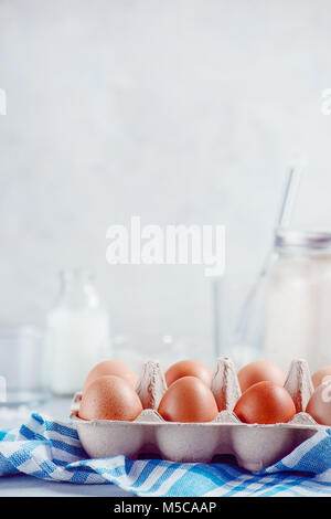 Eggs in a paper tray on a light background with milk, flour and ingredients for Easter cooking. High key background - Stock Photo