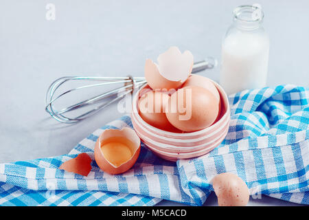 Brown eggs in a ceramic bowl on a light background with milk, flour and ingredients for Easter cooking. High key - Stock Photo