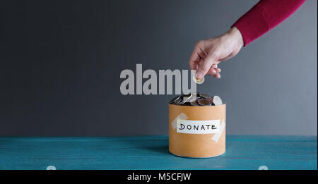 Donation Concept. Hand putting Money Coin into a Donate Box - Stock Photo