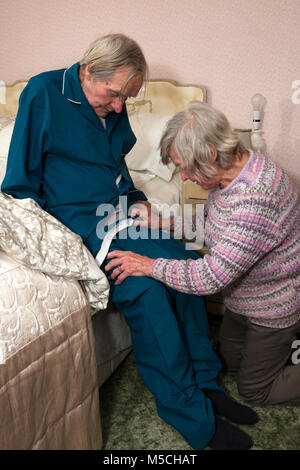 Elderly woman getting her brother ready for bed - Stock Photo