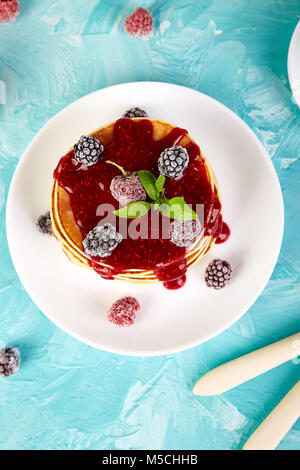 American pancake with jam and frozen raspberry with tea on blue background. Top view. - Stock Photo
