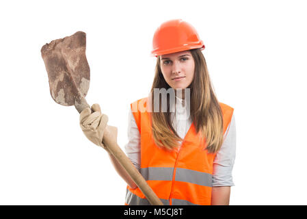 Woman constructor worker holding a dirty shovel after working all day - Stock Photo