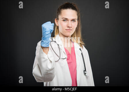 Young doctor portrait  wearing robe making winner gesture with fist on black background - Stock Photo